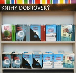 V přilehlém stánku byly Mawerovy knihy v prodeji jak v pevné, tak i v paperbackové vazbě.