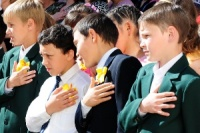 Children place their hands over their hearts during the playing of the Kyrgyz National Anthem marking the beginning the graduation ceremony of the Birdik Village School, Kyrgyzstan, May 25, 2010. Airmen from the Transit Center at Manas, Kyrgyzstan, attended the ceremony to celebrate the accomplishments of the children during the school year. This year was important to the children and the community of Birdik Village because they celebrated the completion of the first school year in the renovated facility. The project, which cost about $540,000, was funded by the Air Force and made possible by volunteer efforts from Airmen at the Transit Center at Manas, Kyrgyzstan. The ribbon cutting was held Sept. 1, 2009.